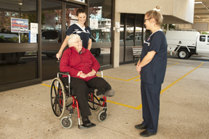 Lady in wheelchair with two nurses
